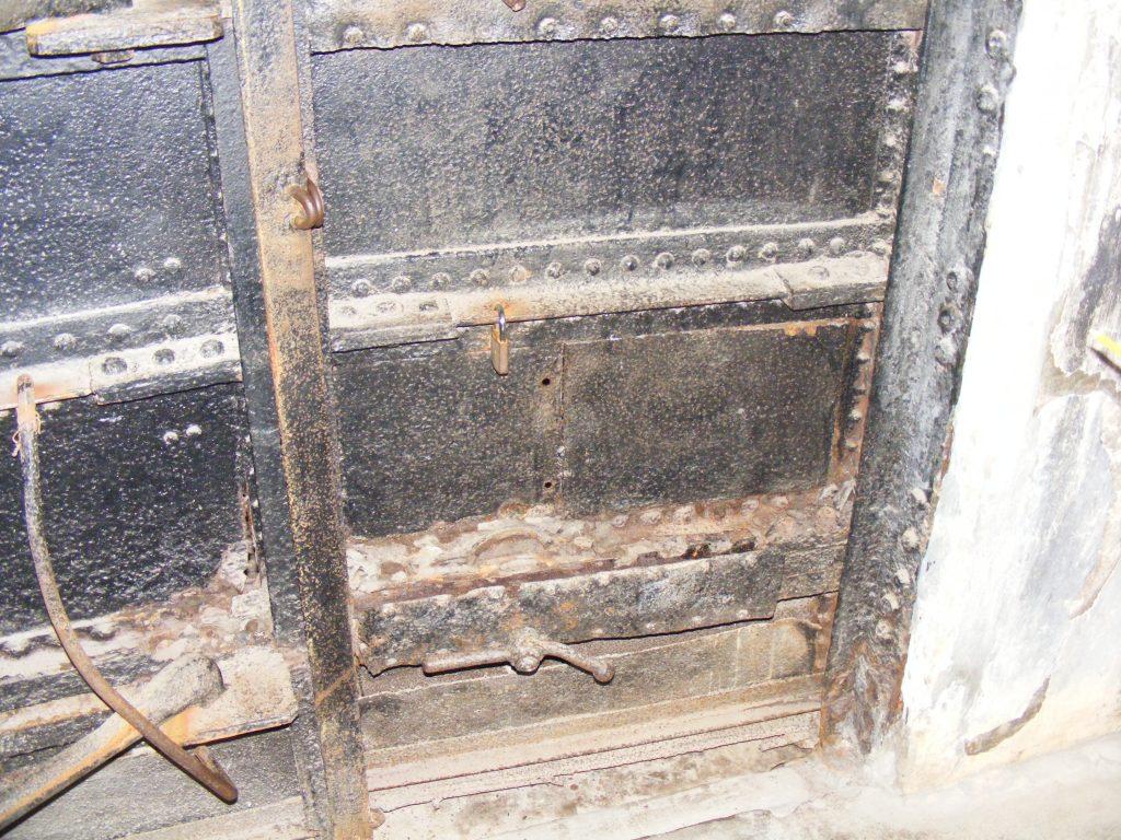 2.Drzwi przez które wydostali się uciekinierzy w 1943 roku. Wyraźnie widać płytę, która zasłania otwór wykonany ręczną wiertarką, fot. Autor