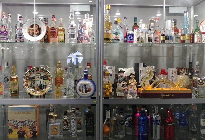 Szklany regał, na którym stoi kilkadziesiąt butelek po wódce oraz inne eksponaty związane z gorzelnictwem.