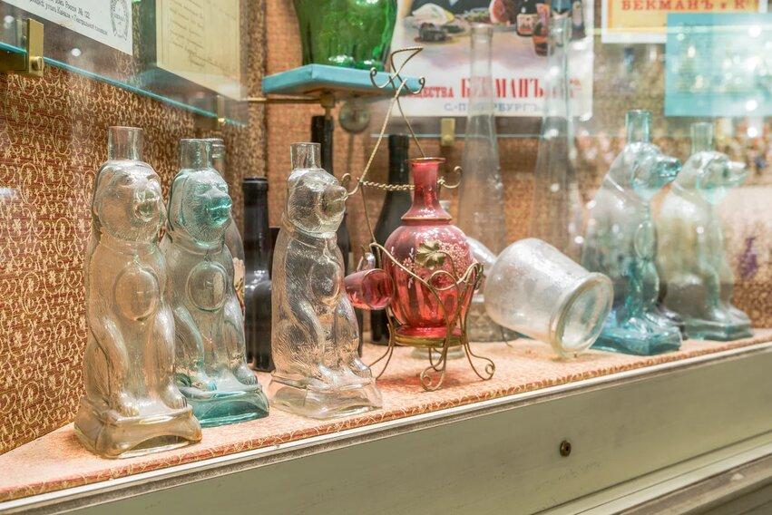 fragment wystawy. kilka butelek w kształcie siedzącego niedźwiedzia, pomiędzy nimi jedna czerwona butelka w metalowym stojaku - ozdobnym koszyku